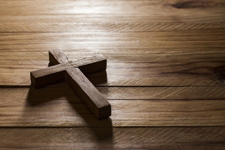 A cross lying on a wood table.