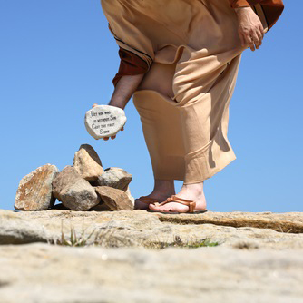 Person holding a rock depicting answer by Jesus from John 8:7.