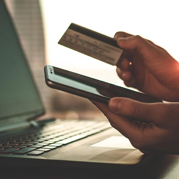 Person holding cellphone and credit card over computer