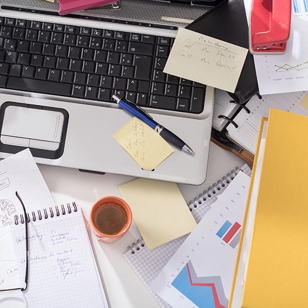 Desk cluttered with paper, computer, notes and more