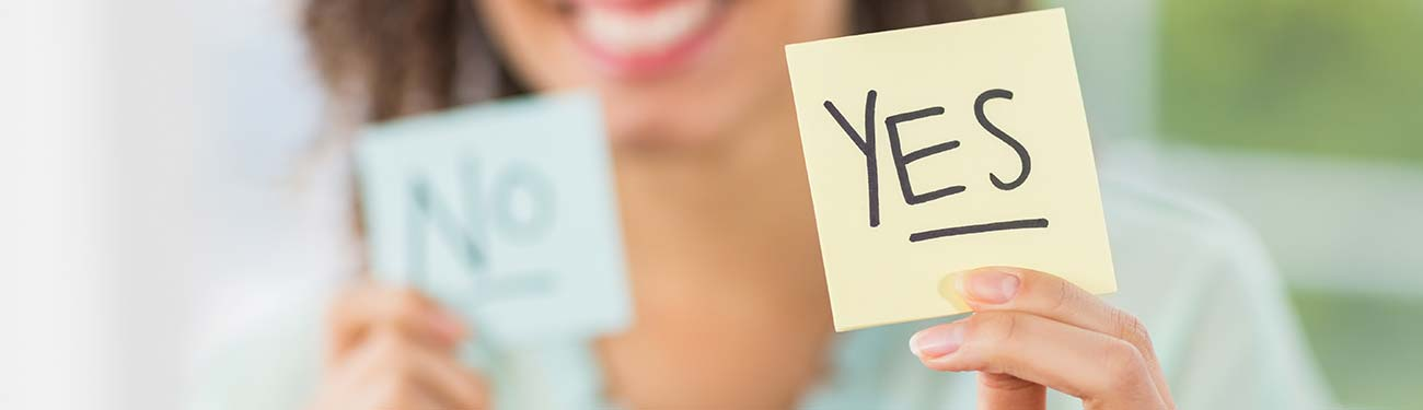 Women holding up post it notes yes or no
